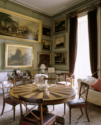 View of the Breakfast Room at Calke Abbey, showing the circular table inlaid with light and dark oak in radiating bands, as well as photographs of Richard Harpur and Sir Vauncey in old age