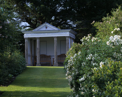 View of the pedimented summer house and flowering white Philadelphus (hydrangeaceae) in the garden at Hinton Ampner in June