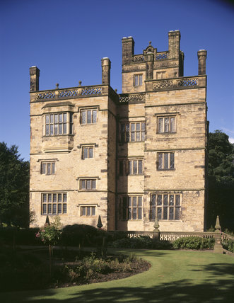 A view of the East Front of Gawthorpe Hall with the lawn and garden in the foreground