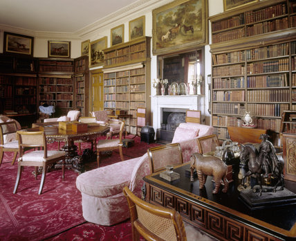 View of the Library at Calke Abbey showing the fireplace, map, scrolls, books, suite of oak furniture (1806-7), set of library chairs with cane seats and octagonal walnut table with lion feet