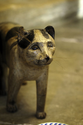 A wooden, life-size model of a black and white cat, given to Charles Wade by Professor Albert Richardson, in the downstairs Living Room at Priest's House, Snowshill Manor