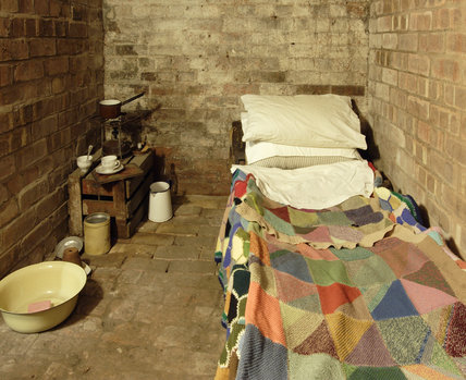 The Second World War air raid shelter at the Birmingham Back to Backs with a knitted blanket over the single bed and a collection of jars and bowls on the floor