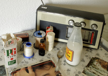 A battery radio, tea-making equipment and some materials in the upper rooms of the 1970s tailor's shop in the Birmingham Back to Backs