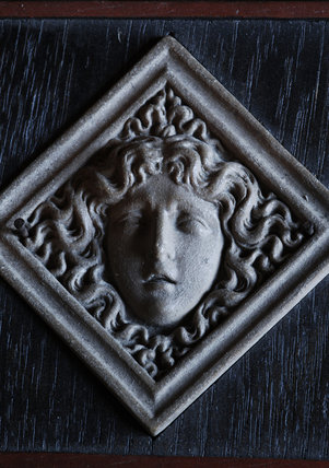 A framed, diamond-shaped stone head, possibly representing Medusa, from Admiral at Snowshill Manor