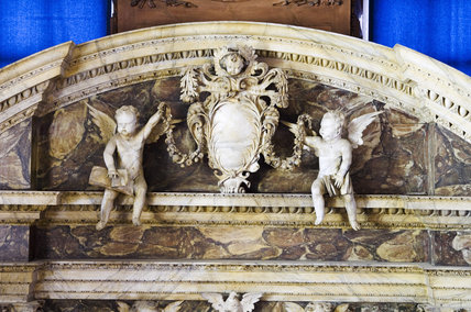 Close view of the broken segmental pediment and putti at the top of the altar in the Chapel at Belton House, Lincolnshire, UK