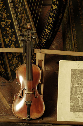 A small violin, part of the musical instrument collection of Charles Paget Wade in the Music Room at Snowshill Manor, Gloucestershire