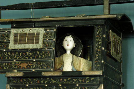 Close view of a Japanese model of a palanquin (litter) with a figure inside, part of Charles Paget Wade's collection, in the Turquoise Hall at Snowshill Manor, Gloucestershire