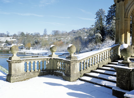 The steps and baluster of the Palladian Bridge at Prior Park Landscape Garden under snow