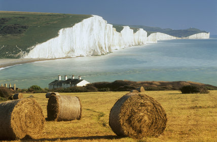 View of bales of hay near hyngton Farm in the foreground, with the spectacular white Seven Sisters cliffs and bright turquoise sea beyond