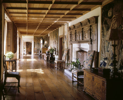 The Long Gallery at Packwood House showing the fireplace, late C17th Italian chairs covered in English bargello needlework, oak floor and tapestries