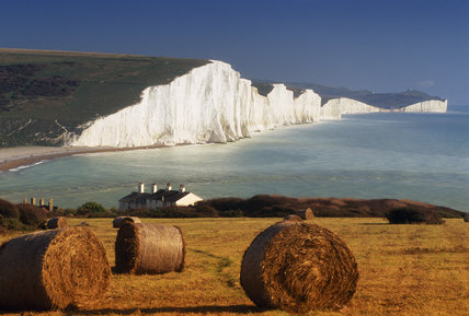 View of bales of hay near Chyngton Farm in the foreground, with the spectacular white Seven Sisters cliffs beyond