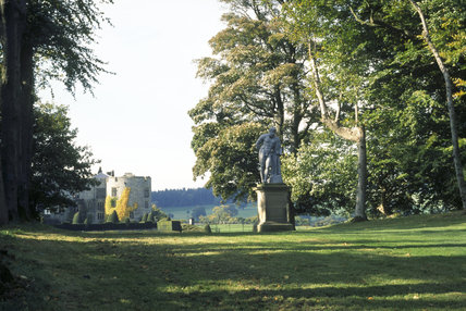 View down the Lime Avenue with Chirk Castle beyond, showing the lead statue of Hercules on a stone plinth