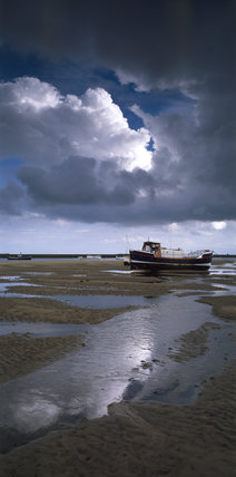 Low tide at Blakeney Point with grey storm clouds looming low