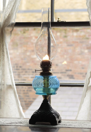A glass oil lamp  on a windowsill of the 1870s house in the Birmingham Back to Backs