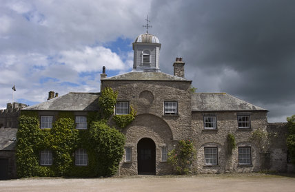 The domestic offices from the Courtyard at Sizergh Castle, Cumbria with an arched entrance in the limestone walls