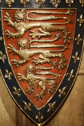 Close view of a moulded and painted shield with three gold lions on a red background, in Meridian at Snowshill Manor, home of collector Charles Wade