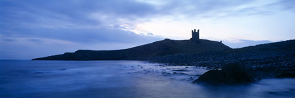View across Embleton bay at dawn towards Dunstanburgh castle