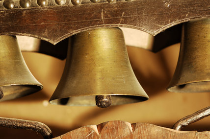 A set of carriage bells beneath a leather canopy, used and made by Charles Wade as a door bell, in the Lobby at Snowshill Manor