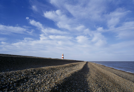 A view along the shingle beach with the Lighthouse in the distance