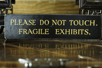 Please Do Not Touch sign on a glass display case at Snowshill Manor, Gloucestershire