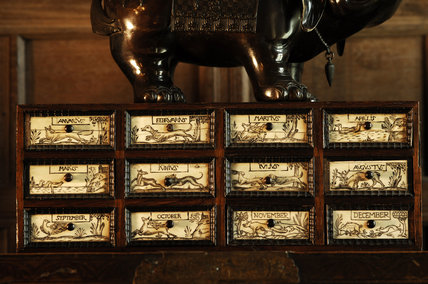 A set of drawers with the months of the year carved on them, part of the Chales Wade collection at Snowshill Manor, Gloucestershire