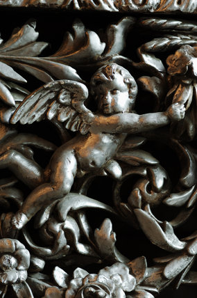 Close view of a carving of a cherub, part of the Chales Wade collection at Snowshill Manor, Gloucestershire