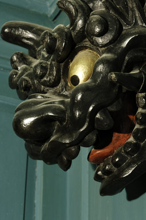 A carved wooden head of a dragon or mythical beast, part of Charles Paget Wade's collection, in the Turquoise Hall at Snowshill Manor, Gloucestershire