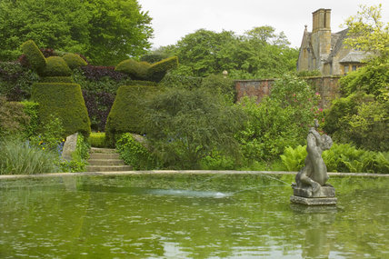 Looking over the water in the Bathing Pool Garden at Hidcote Manor Garden, Gloucestershire, with the bird topiary and the house itself in the background
