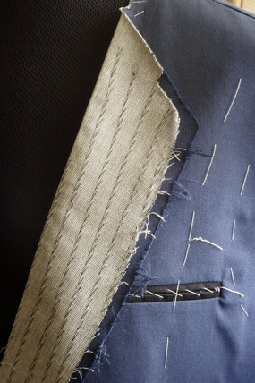 Close view of the lapel of a jacket being made in the upper rooms of the 1970s tailor's shop in the Birmingham Back to Backs