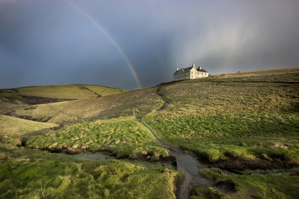 Rainbow and remote house near Port Quin, Cornwall.