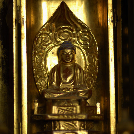 Close view of a carved and gilded figure of Kwannon the Dhyani Bodhisativa staning in a lotus flower, in the Green Room at Snowshill Manor