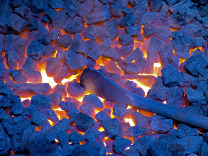 A steel bar heating in the glowing coals of the forge at Finch Foundry where hand tools were produced in the C19th and C20th