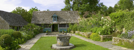 The Well Court at Snowshill Manor, Gloucestershire, UK with a Venetian well-head on the lawn and a statue of the Virgin Mary in a gable of the summer-house