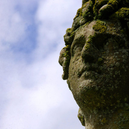 Close view of stone sculpture head in the garden at Mottisfont Abbey
