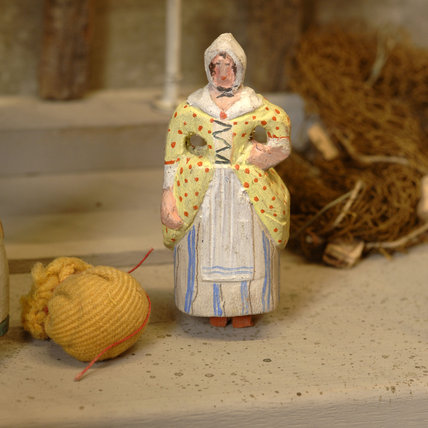 Close view of a model woman, part of the reconstruction of Wolf's Cove, the model village which was once in the garden at Snowshill Manor but is now in the room known as Occidens