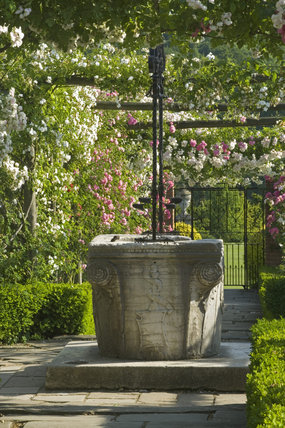 Close view of the well-head framed by the rose pergolas in the Walled Garden at Polesden Lacey, Surrey