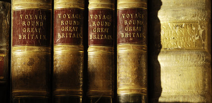 Close view of the spines of a collection of books in Ann's Room at Snowshill Manor