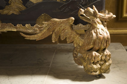 Close view of a George II giltwood dragon supporting a Japanese lacquer coffer in the Staircase Hall at Belton House, Lincolnshire, UK