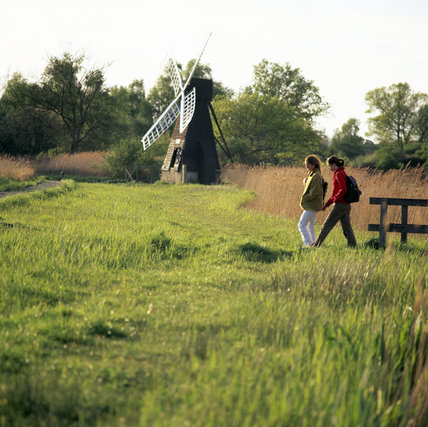 View of wind pump (windmill) and visitors walking at Wicken Fen, Cambridgeshire