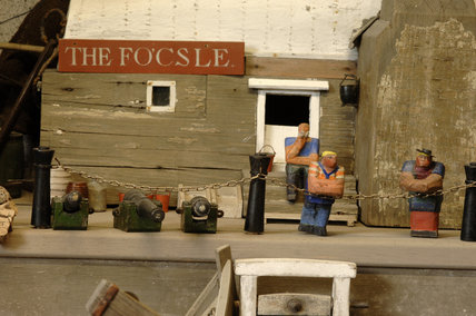 Close view of three wooden figures in front of The Focsle, part of the reconstruction of Wolf's Cove, the model village which was once in the garden at Snowshill Manor but is now in the room known as Occidens