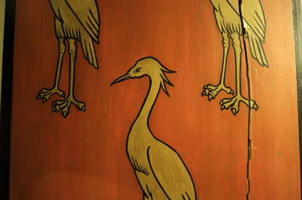 Close detail of the painted decoration on a wooden shield with three gold cranes in the Front Staircase and Green Room Corridor at Snowshill Manor