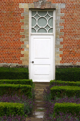 White door with patterned glass window above on the south front at Mottisfont Abbey, with clipped hedging of the parterre in the foreground