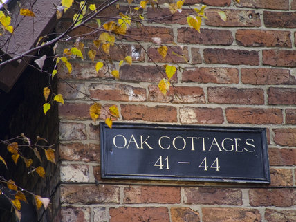 Sign on the exterior of Oak Cottages, built for the mill workers at Quarry Bank Mill, Styal
