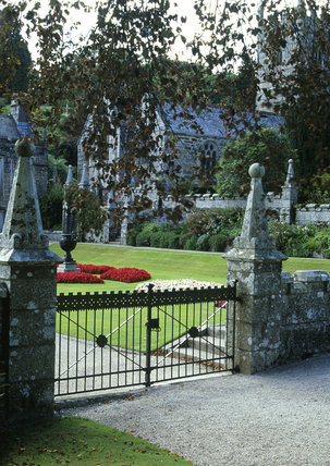 A view through the garden gate at Lanhydrock, Cornwall, offering a glimpse of the begonia bedding and the C15th church, dedicated to St Hydroc,  in the distance