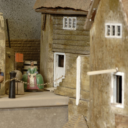Close view of a model of a woman in front of the warehouse, part of the reconstruction of Wolf's Cove, the model village which was once in the garden at Snowshill Manor but is now in the room known as Occidens