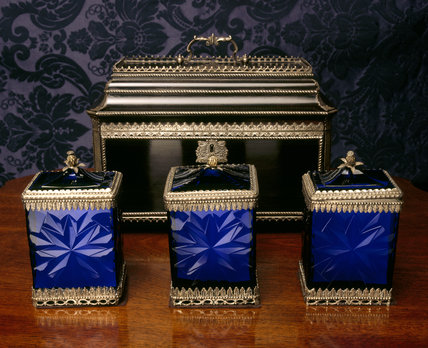 A set of three blue glass Tea Caddies and covers, mounted in silver, ebony case behind, mid C18th