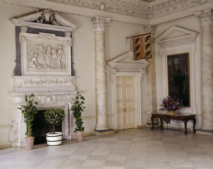 Partial view of The Marble Hall right hand of the fireplace, chimneypiece by Rysbrack (dated about 1736),painting of a cassowary by Francis Barlow,and family flag above the door
