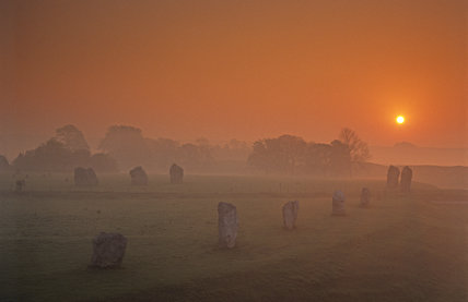 Dawn at Avebury Stone Circle with two stones against a misty landscape with the sun rising in a pink-orange sky