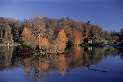 View across deep blue lake at Stourhead with temples in far distance amidst autumn trees against a blue sky