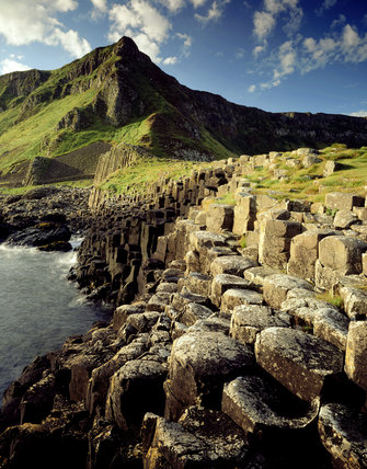 A view of the dramatic coastline at the Giant's Causeway taken in the sunshine with rocks visible in the foreground